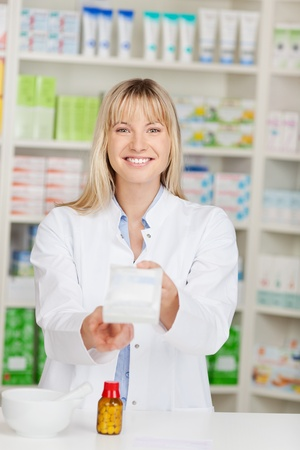 passing over: female pharmacist passing medicine box over the counter