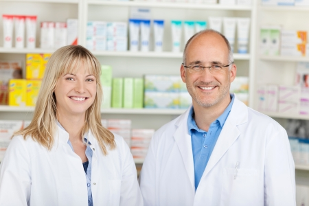 male and female pharmacist standing against shelves with medicine photo