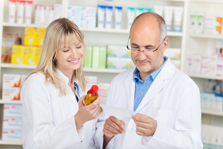 Mature pharmacist with female coworker holding medicine and prescription paper in pharmacy photo