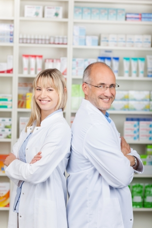 smiling pharmacists standing back to back with crossed arms photo