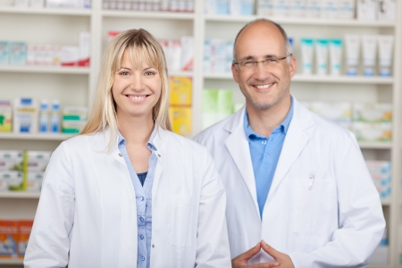 Portrait of confident male and female pharmacists standing together in pharmacy