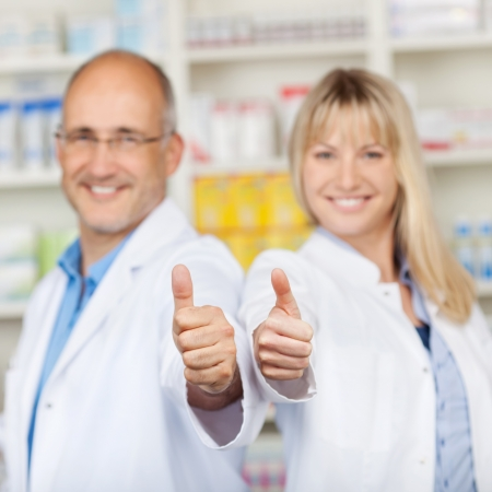 Portrait of male and female pharmacists showing thumbs up in pharmacy photo