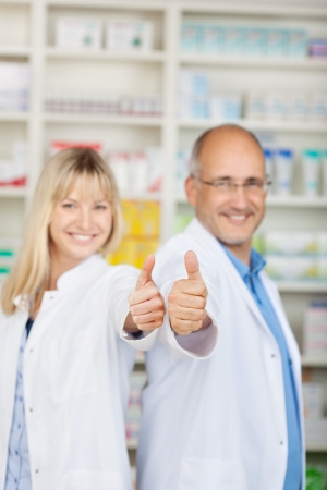 female and male pharmacist in pharmacy showing thumbs up photo