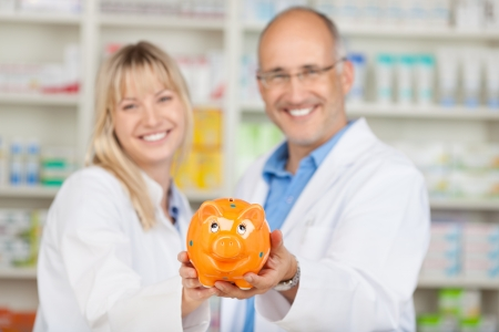 Portrait of happy male and female pharmacists holding yellow piggybank in pharmacy photo