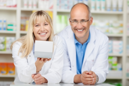 two phamacists leaning at hte counter, presenting medicin box photo