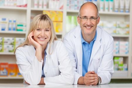 drugstore: Retrato de farmacéuticos macho y hembra apoyándose en mostrador de la farmacia