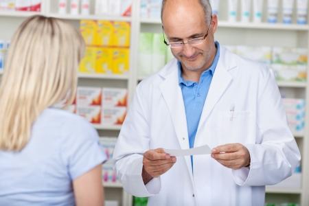 farmacéutico hombre leyendo receta mientras el cliente está esperando en el mostrador