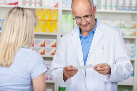 male pharmacist reading prescription while client is waiting at the counter photo