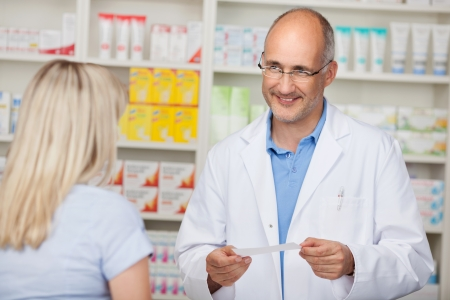 pharmacy store: confident mature pharmacist in customer interview with woman