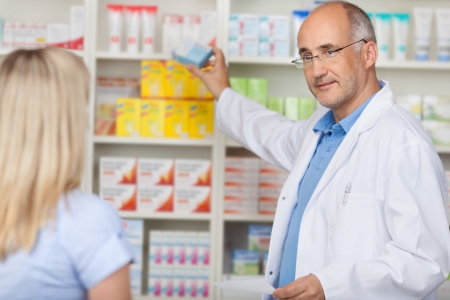 pharmacist talking to female client while taking medicine of the shelf Imagens