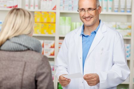 Male pharmacist holding prescription paper while looking at customer in pharmacy photo