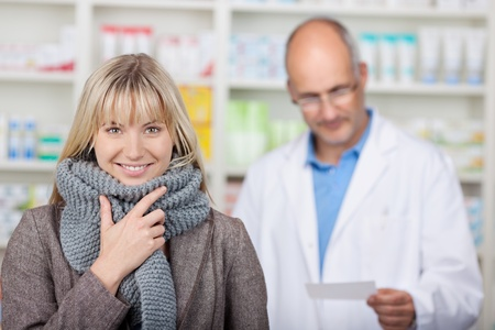 smiling client with scarf in pharmacy with pharmacist in background photo