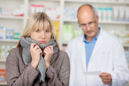 Portrait of young woman shivering with male pharmacists reading prescription paper at pharmacy photo