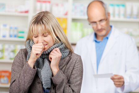 blond female costumer suffering from cold in pharmacy photo