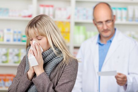 Young female customer suffering from cold with pharmacist reading prescription paper in background at pharmacy photo