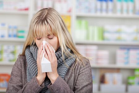 Young female customer suffering from cold in pharmacy photo