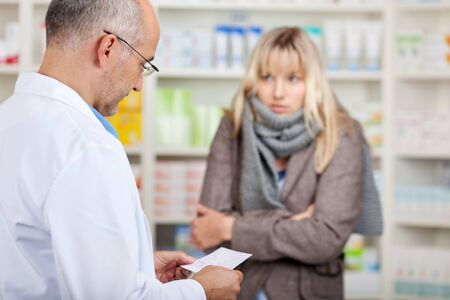 Mature pharmacist reading prescription while female customer shivering in pharmacy photo