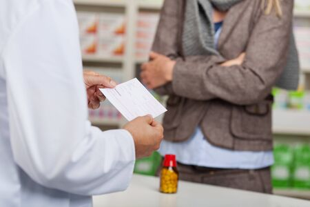 pharmacist reading prescription paper at the counter photo