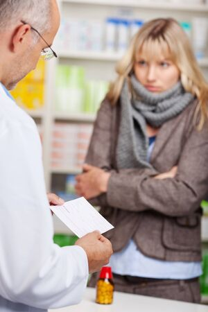 pharmacist and woman with a cold in pharmacy photo