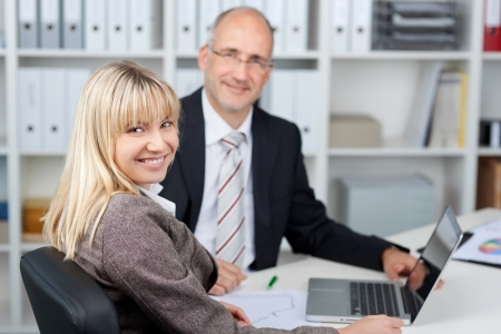 coworkers: Portrait of businesswoman sitting with male coworker at office table Stock Photo
