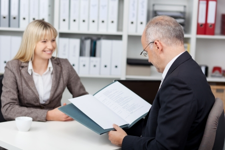 cv: manager reading woman´s cv at office desk Stock Photo