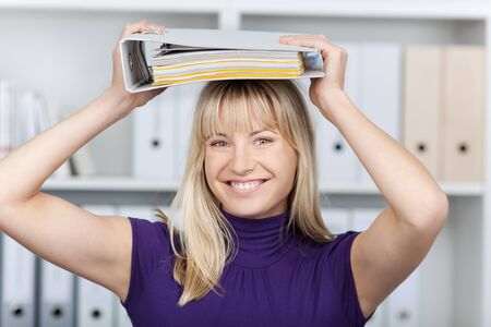 fringes: Portrait of happy young businesswoman placing binder on head in office Stock Photo