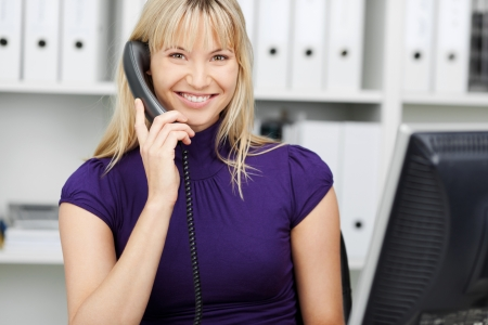 front office: Portrait of confident businesswoman conversing on landline phone in office Stock Photo