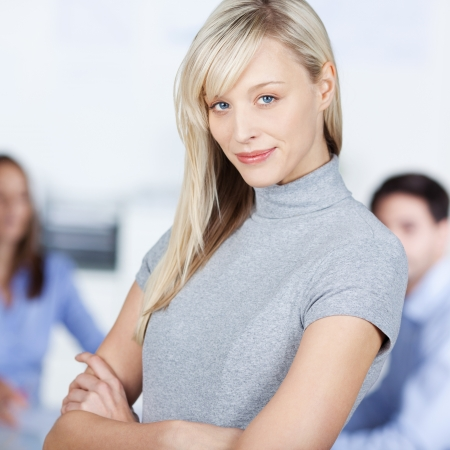 Portrait of confident businesswoman with arms crossed against colleagues in office photo