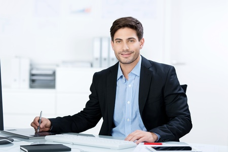Portrait of mid adult businessman working at desk in office photo