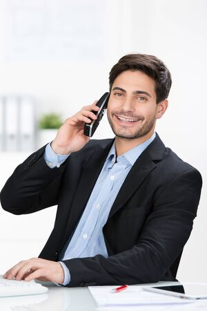 cordless: Portrait of happy businessman using cordless phone at desk in office