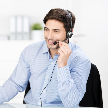 service desk: Mid adult male customer service operator communicating on headset at desk in office