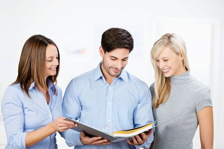 Happy businesspeople reading documents together in binder at office Stock Photo - 21246637