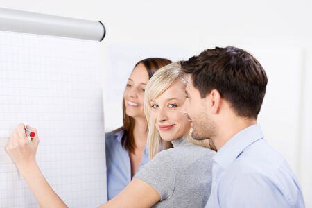 flip chart: Portrait of mid adult businesswoman writing on presentation board with coworkers looking at it in office Stock Photo