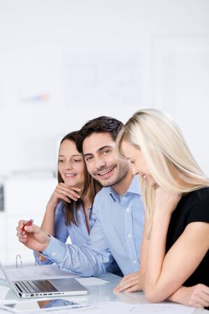Portrait of mid adult businessman with female coworkers in a meeting at office desk photo