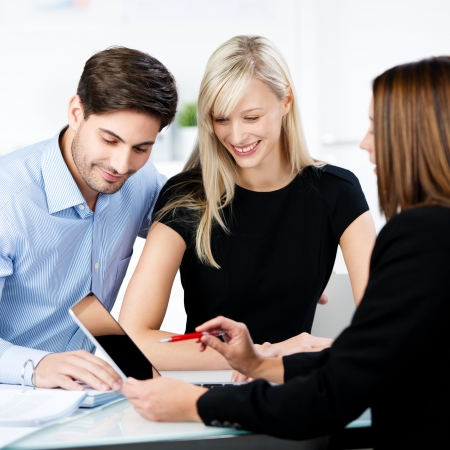 Financial advisor explaining to couple while pointing at digital tablet at desk in office photo