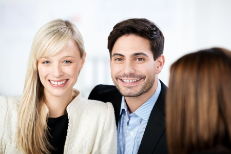 Portrait of confident mid adult couple smiling with financial advisor in foreground photo