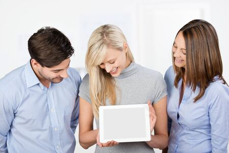 Happy mid adult businesswoman holding digital tablet while coworkers looking at it in office photo