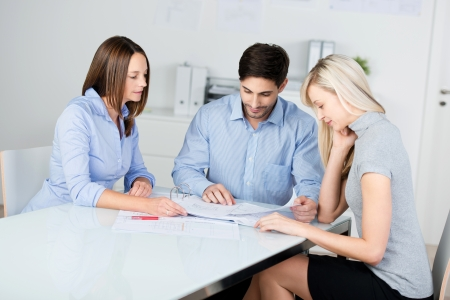 Happy businesspeople discussing over blueprint at conference desk in office photo
