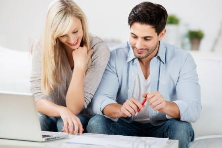 Mid adult couple with laptop looking at document on table at home