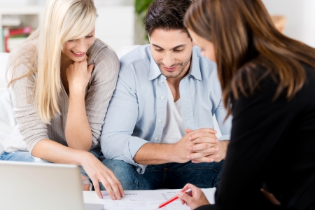 banker: Female financial advisor explaining document to mid adult couple at table in house