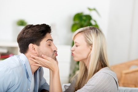 joking: Side view of mid adult couple puckering lips at home