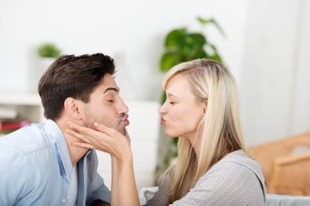 besos apasionados: Vista lateral de mediados de adulto joven fruncir los labios en su casa