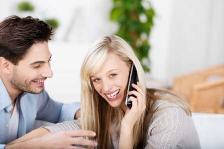 cordless: Portrait of happy mid adult woman conversing on cordless phone while man looking at her in house Stock Photo