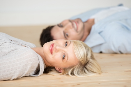 Portrait of beautiful woman smiling with man lying on hardwood floor at home photo