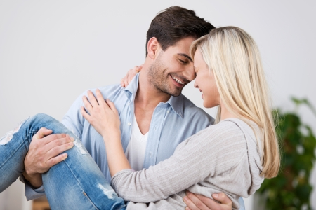 Happy mid adult man carrying woman in house photo