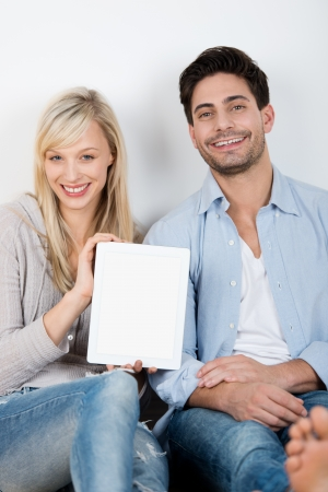 Portrait of happy mid adult couple with digital tablet sitting against wall photo