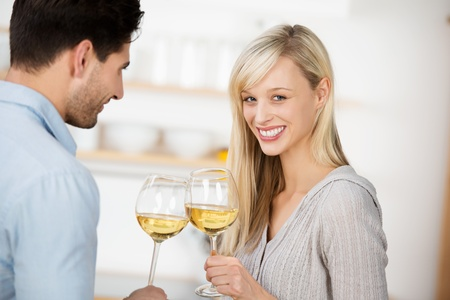 Young couple drinking white wine in elegant long stemmed wineglasses with the beautiful young blond woman looking atthe camera with a lovely smile photo