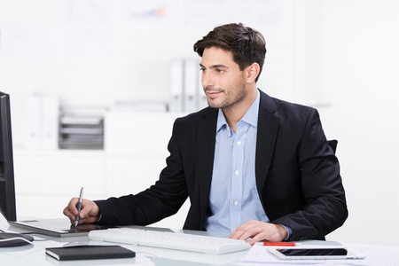 businessman working at his computer: Handsome young businessman sitting at his desk in the office working on a desktop computer using a tablet and stylus