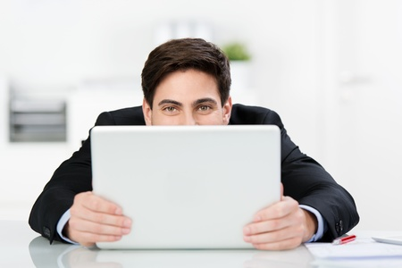 peeping: Smiling man hiding behind his laptop peeping over the top with smiling eyes as he sits at his desk Stock Photo