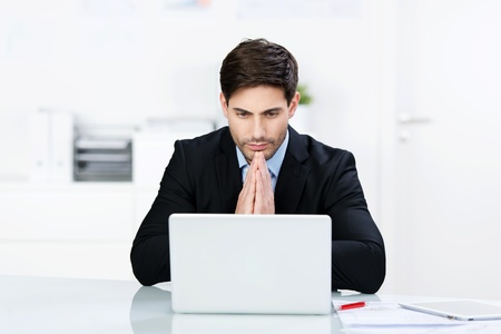 doubt: Businessman reading information on his laptop sitting with his palms together engrossed in the content Stock Photo